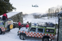 Lake-District;Cumbria;National-Park;UK;hill;winter;cold;snow;snowpack;freezing;weather;mountain;mountain-rescue;rescue;paramedic;air-ambulance;doctor;treatment;casualty;injured;emergency-services;team-work;stretcher;evacuation;high-vis;yellow;Langdale;helicopter;air-ambulance;down-draught;spindrift;flying