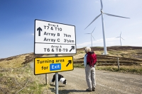 Southern-Uplands;Biggar;Scotland;UK;hill;moor;moorland;sky;blue;climate-change;carbon;Borders;wind-turbine;wind-farm;renewable;renewable-energy;Clyde-Wind-farm;blade;turbine-blade;wind-energy;wind-power;carbon-neutral;clean;green;global-warming;electricity;generating;generation;woman;female;walker;walking;hill-walking;dog;pet;Border-Collie;signage;sign;sign-post;yellow;colourful;array;exit;turning-area